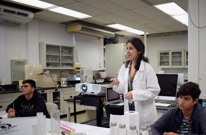 "Adriana Santiago-Ruiz (Middle): Explaining details of the materials science experiment to the high school participants at ""Experimenta con PREM"""